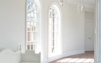 alley with herringbone brick floor, white wall, white framed tall window, clear glass pednant, white bench