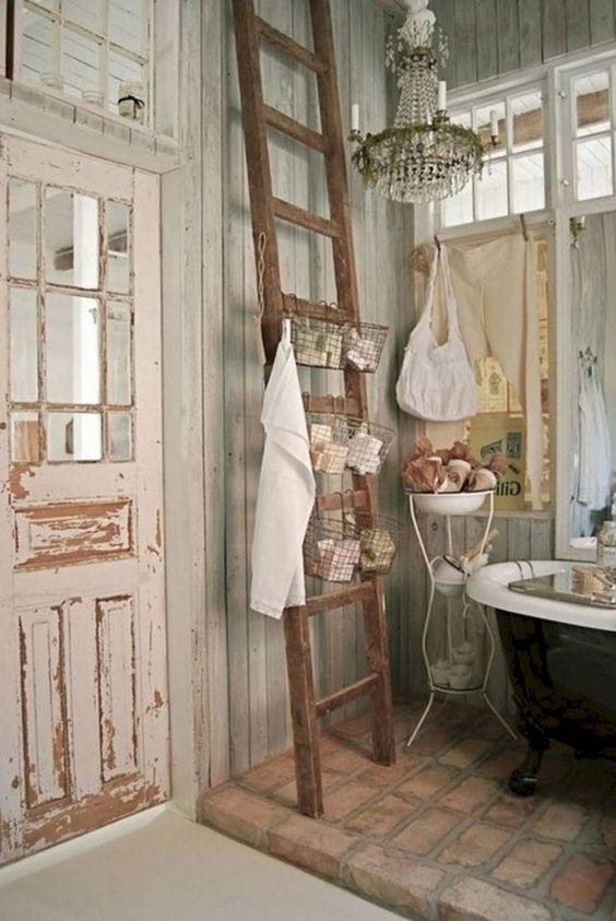 bathroom, brick floor tiles, wooden wall, balck tub, wooden rack, wooden door, chandelier