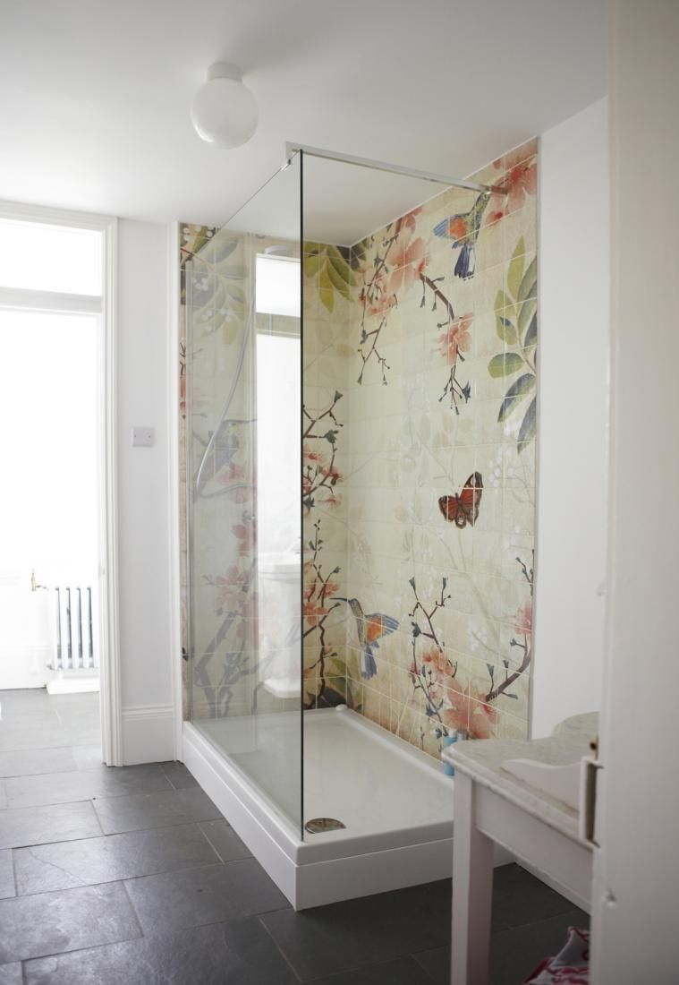 bathroom, grey floor, white wall, flowery wall tiles on the shower