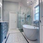 Bathroom, White Marble Floor, White Patterned Floor Tiles, White Wall, Chandelier, White Tub, Shower Area, Blue Cabinet