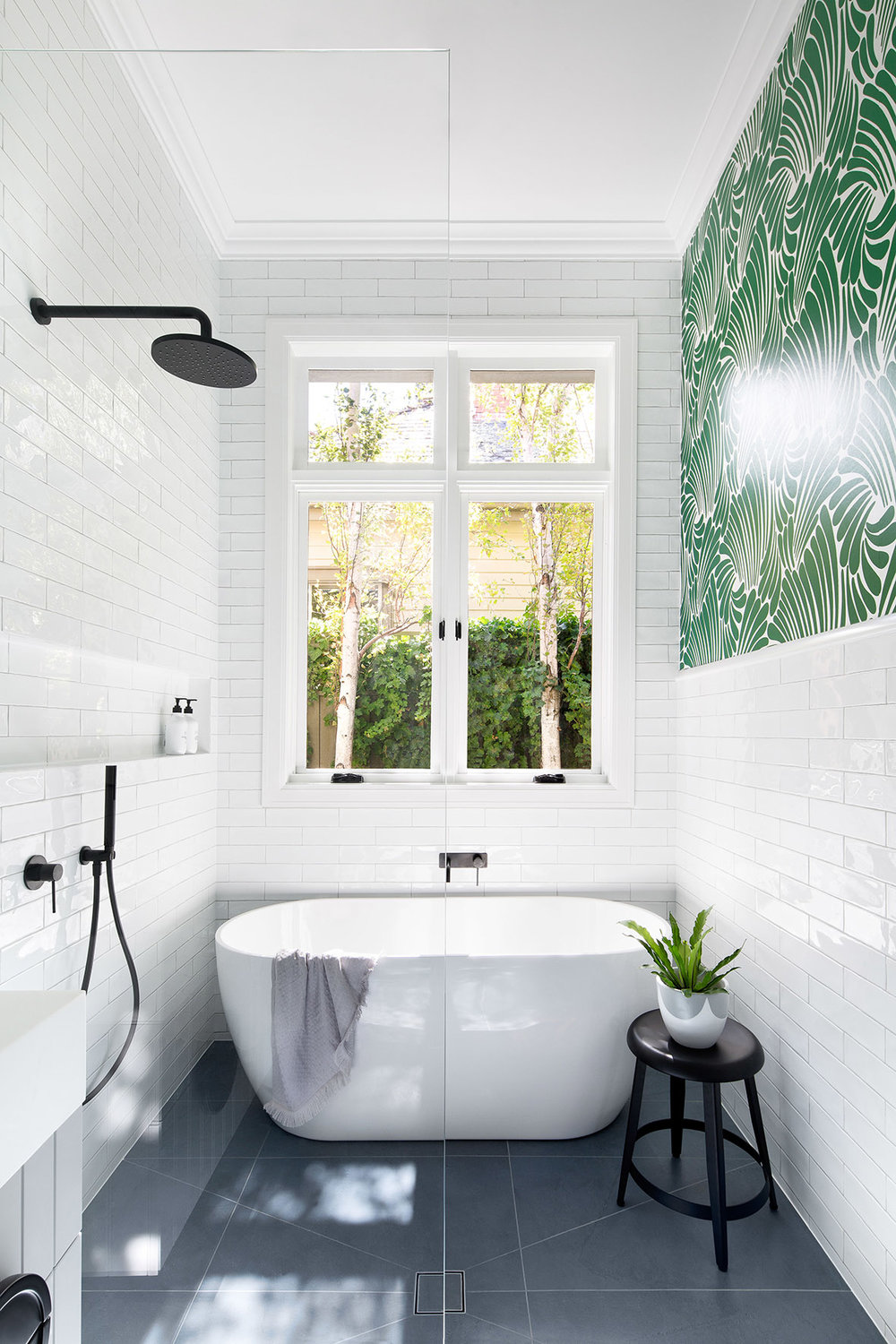 bathroom, white subway wall tiles, grey floor tiles, white tub, white sink, black faucet, green wallpaper accent