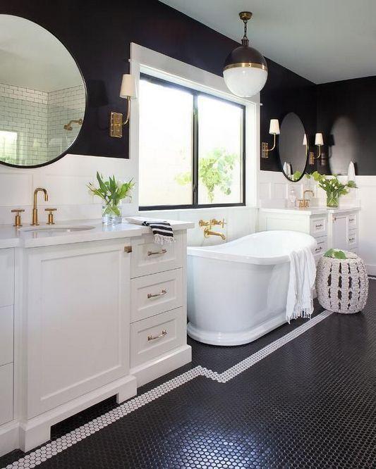 bathroom, white wainscoting, black wall, white black pendant, white cabinet, white tub, mirror, black tniy hexagonal tiles with the white