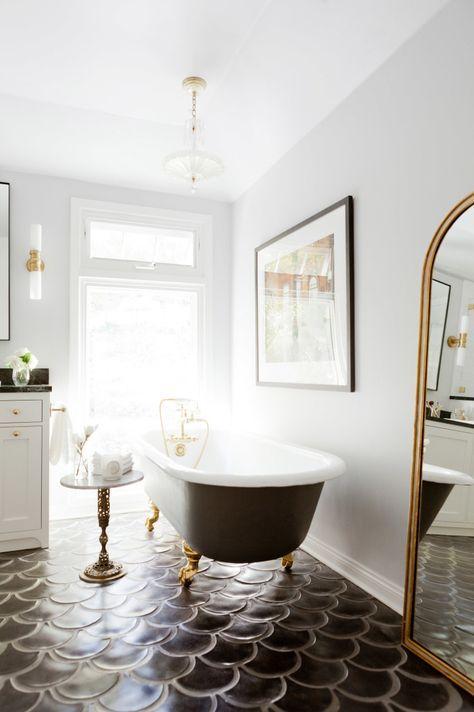 bathroom, white wall, black tub, white cabinet, golden framed mirror, black fish scale floor tiles, golden side table, white pendant, white sconce