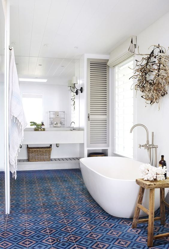 bathroom, white wall, white wub, white sink, shelves, white sconce, blue patterned floor tiles