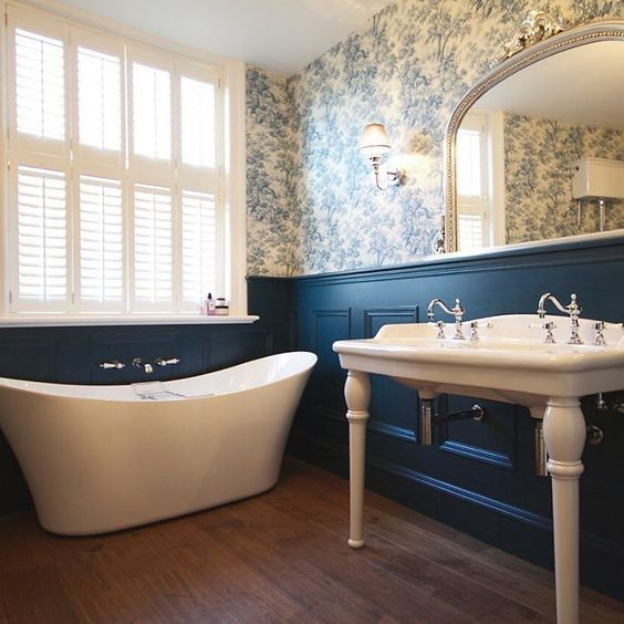 bathroom, wooden floor, flower wallpaper, blue wainscoting, white tub, white sink