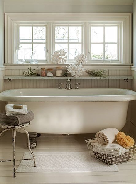 bathroom, wooden floor, white tub, white framed window, white wooden wainscoting