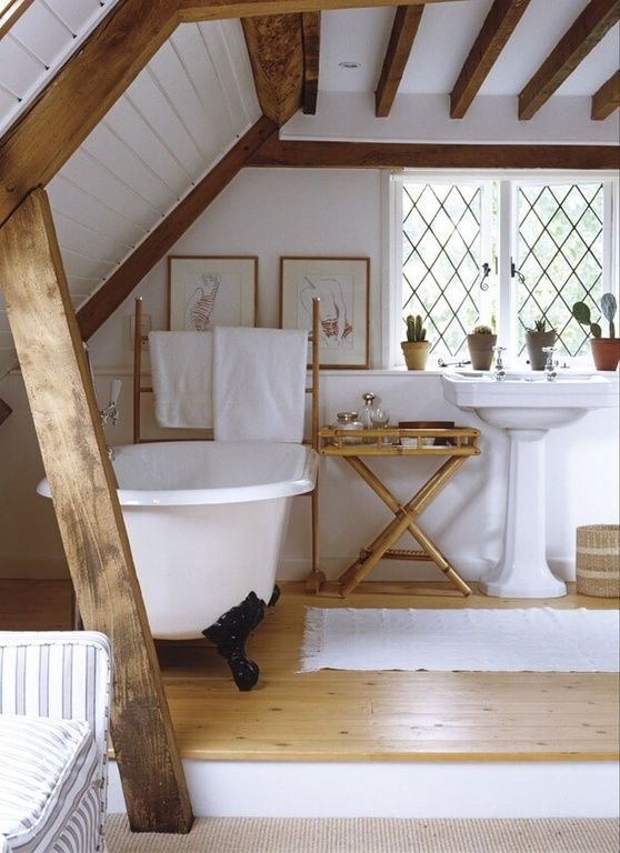 bathroom, wooden floor, white tub, white rug, white sink, white wall, sloping ceiling, wooden beams