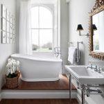 Bathroom, Wooden Floor, White Wall, Arch Window, White Tub, White Sink, Golden Framed Mirror