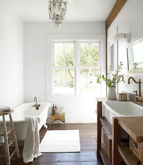 bathroom, wooden floor, white wall, chandelier, wooden vanity, white tub, white rug