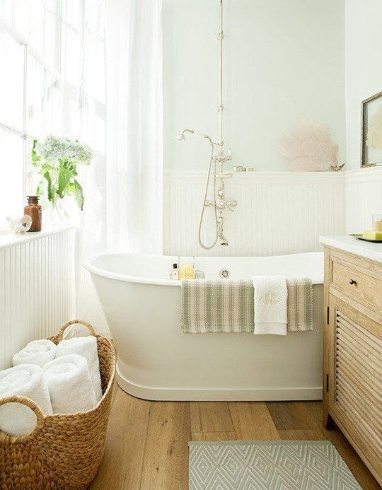 bathroom, wooden floor, white wall, white tub, white wainscoting, wooden cabinet, rattan basket