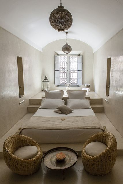 bedroom, beige floor, beige wall, white ceiling, low bed, stage, window, rattan low chairs, moroccan pendants