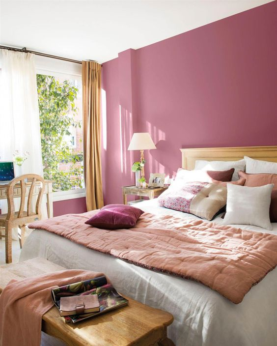 bedroom, white floor, pink wall, white bedding, wooden bench, wooden headboard, wooden study table and chair, mustard cushion
