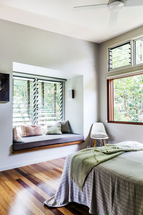 bedroom, wooden floor, white wall, bed with striped bedding, window bay, wooden seating with cushion, large glass wall