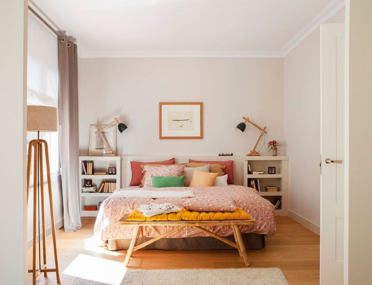 bedroom, wooden floor, white wall, white side shelves, table lamp, pink bedding, bamboo bench, floor lamp, white rug, grey cushion