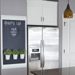 Black Board Decoration On The Wall With Small Plants With White Pots, Grey Wall, Silver Fridge, Black Marble Kitchen Top