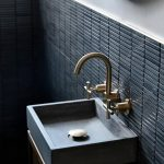 Black Horizontal Lines Backsplash, Grey Wall, Grey Square Sink, Golden Faucet, Wooden Cabinet