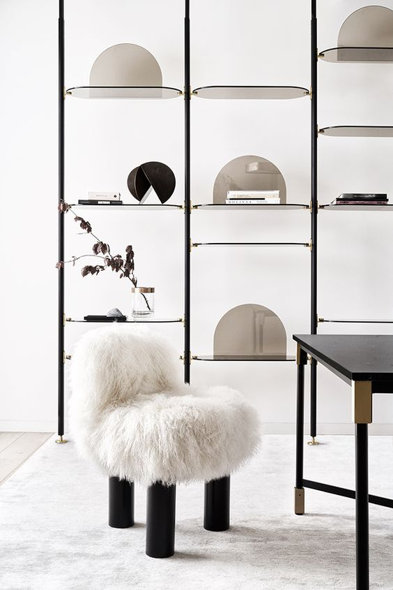 black lanky metal with glass curvy tray, white wall, white furry stool, black table