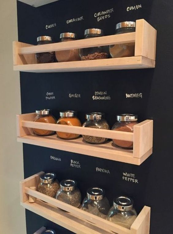 black wall, wooden floating shelves, seasoning bottles