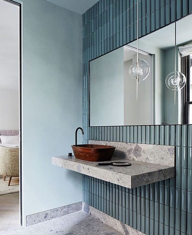 blue vertical backsplash tiles, grey floor, blue wall, rectangular mirror, glass pendant, floating grey vanity, wooden sink