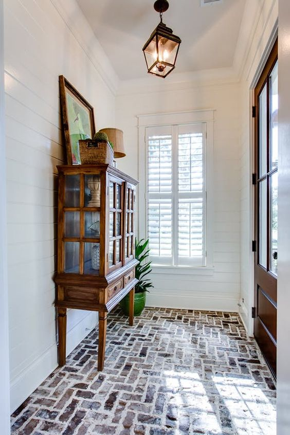 brick herringbone floor on the entrance, white plank wall, pednant, wooden cabinet