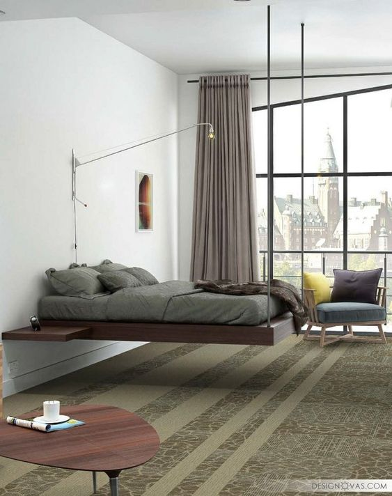 brown floating bed, wooden side table, logn sconce, green rug, blue chair, large glass window