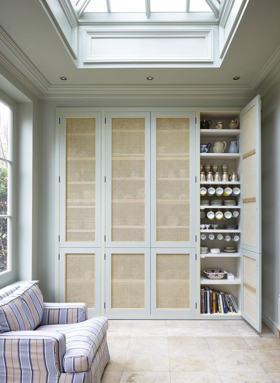 built in cupboard storage with rattan doors, floor tiles, white wall, white ceiling, glass ceiling, striped bench