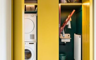 built in cupboard with yellow doors, gren inside, laundry machines, shelves, glass pendant, white floor