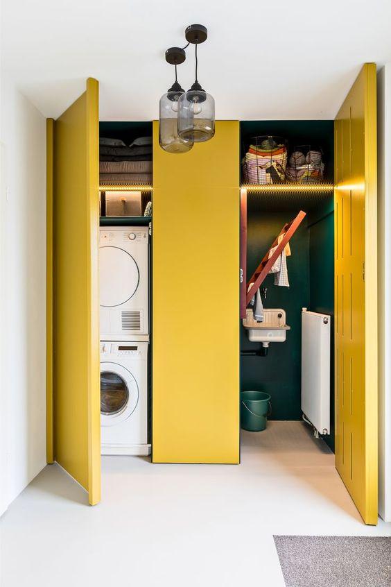 built in cupboard with yellow doors, gren inside, laundry machines, shelves, glass pendant, white floor