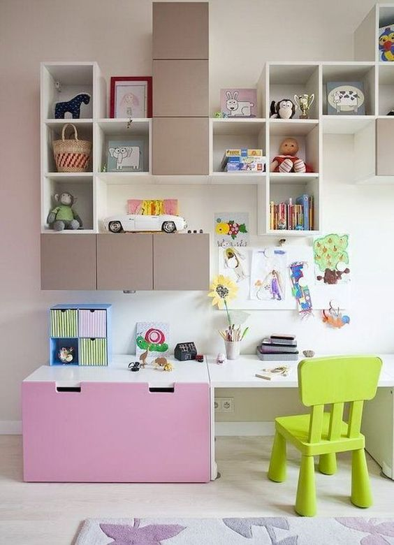 children study, white floor, white wall, small box shelves, white board table with pink storage, green low chair