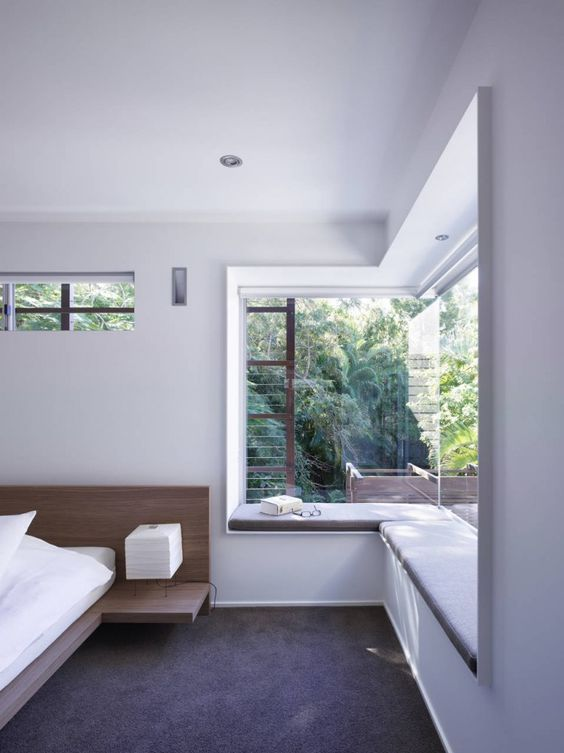 clear glass on the corner of a bedroom, window nook, grey cushion, dark floor, wooden bed platform