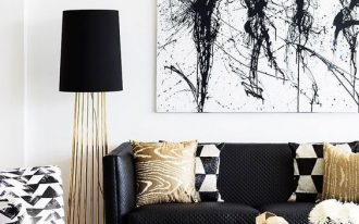 contemporary living room, white wall, white floor, black rug, glass coffee table with golden support, black covered floor lamp with golden legs, black sofa, golden chandelier