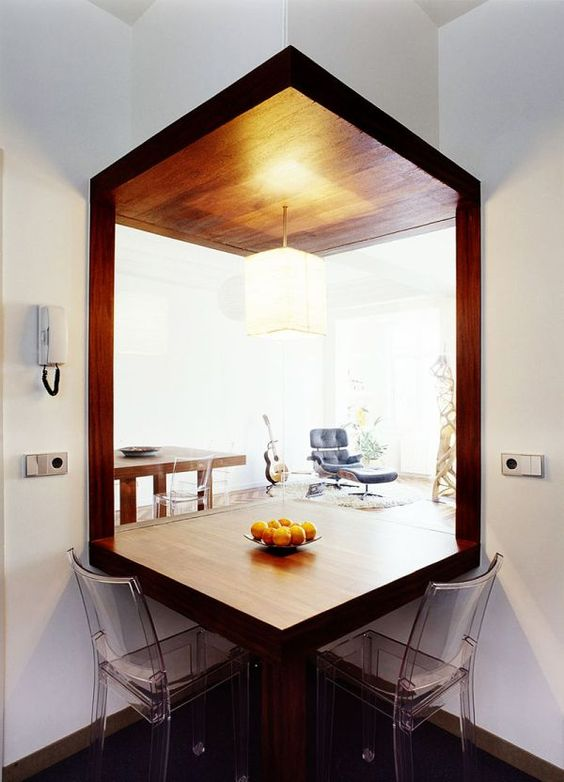 cornered clear glass, white wall, corner wooden table, acrylic chair, dark floor, pendant