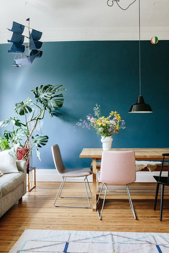 dining rom, wooden floor, gree wall, pink chairs, wooden table, black pendant, white rug, grey sofa
