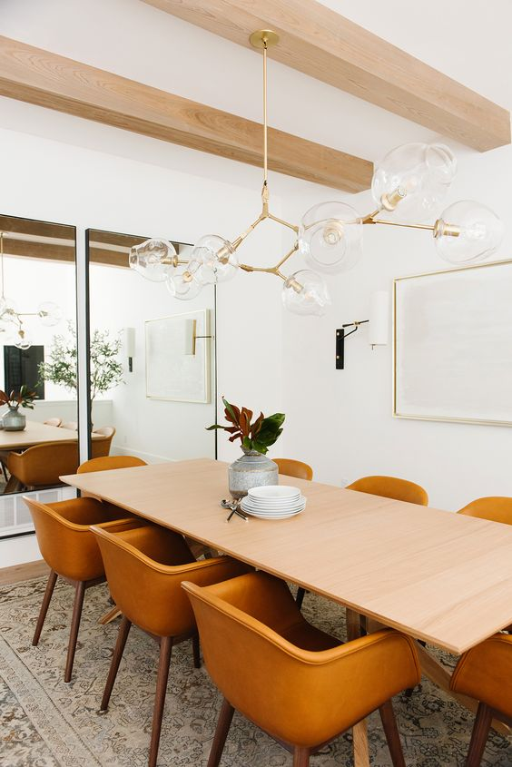 dining room, white floor, brown patterned rug, white wall, white ceiling, wooden beams, glass pendants, wooden table, orange chairs