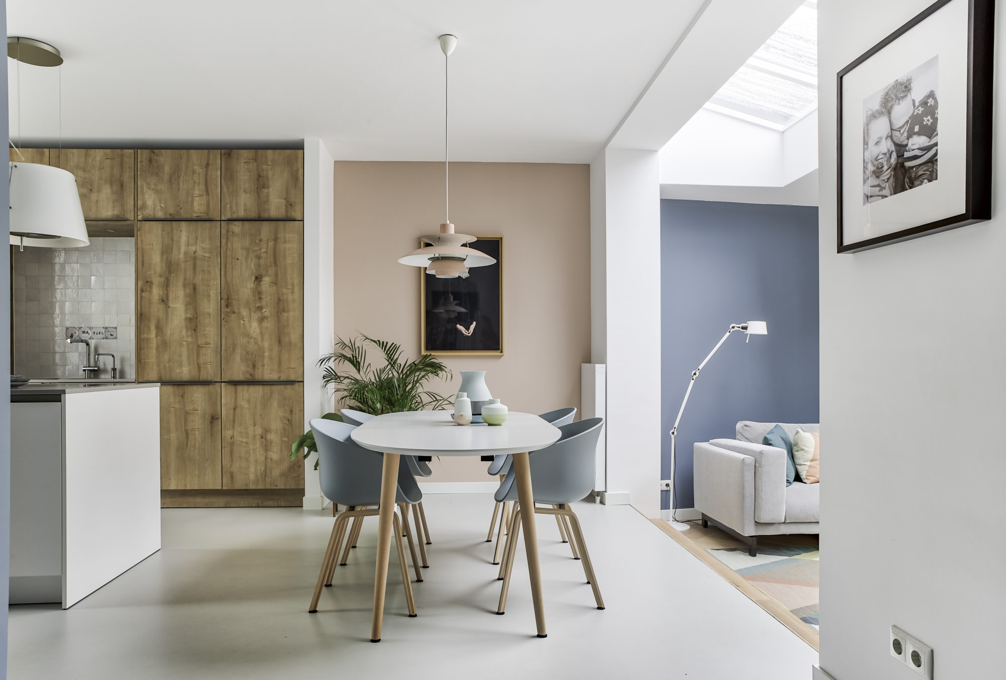dining room, white floor, pink accent wall, open kitchen, white table, blue chair, pendant