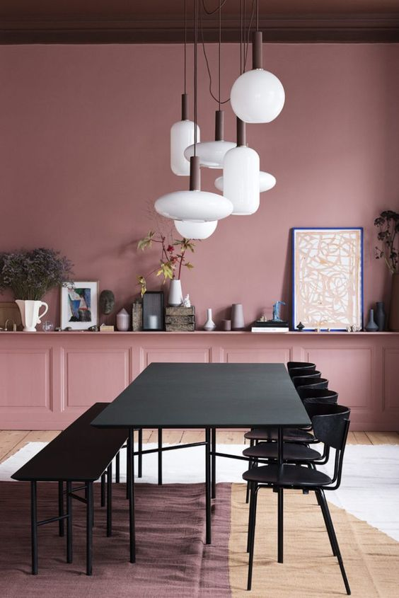 dining room, wooden floor, white brown rug, pink wall, pink shelves, white pendants, black table, black chairs, black bench