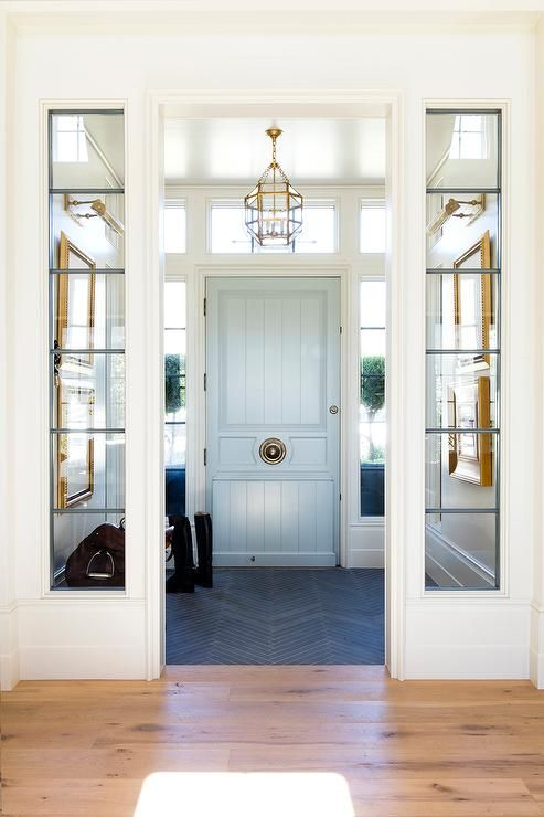 entrance, white framed window and wall parition, chandelier, light blue door, blue chevron floor tiles, white ceiling
