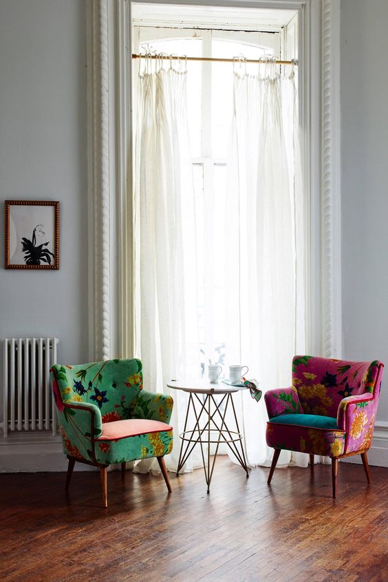 green and pink chairs with flowery pattern, wooden floor, round side table, white wall, white curtain