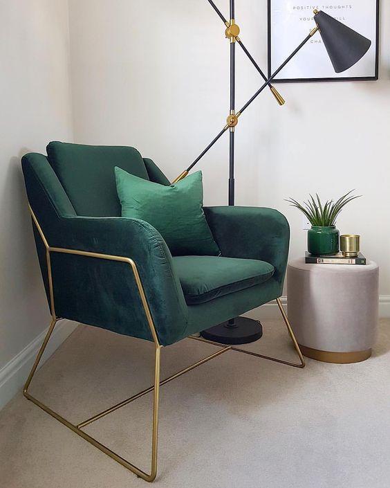green chair with golden metal support, seamless floor, beige wall, beige ottoman, black floor lamp