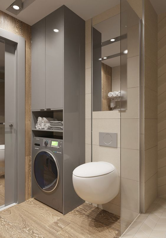 grey laundry machine, grey built in tall storage, wooden floor, beige wall tiles, white floating toilet