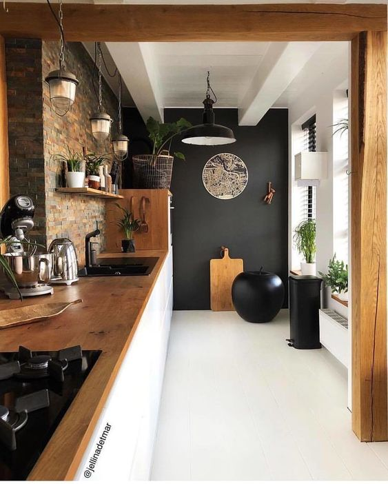 kitchen, white floor, black wall, brown tiles wall, white cabinet, wooden top, black pendant, rustic pendant