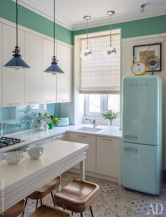 kitchen, white patterned floor, white kitchen cabinet, blue pendant, white dining table, wooden stools, blue backsplash, blue fridge, green wall