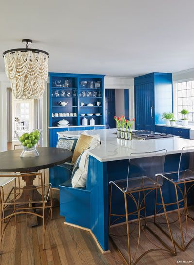 kitchen, wooden floor, blue cabinet, blue island with white marble top, acrylic stools, dining set ont he side, chandelier