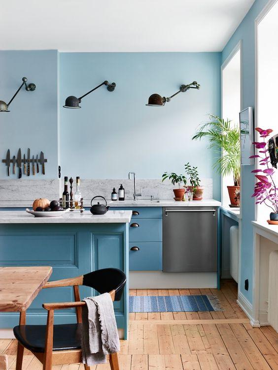 kitchen, wooden floor, blue wall, blue wooden cabinet, grey marble backsplash, black sconces,