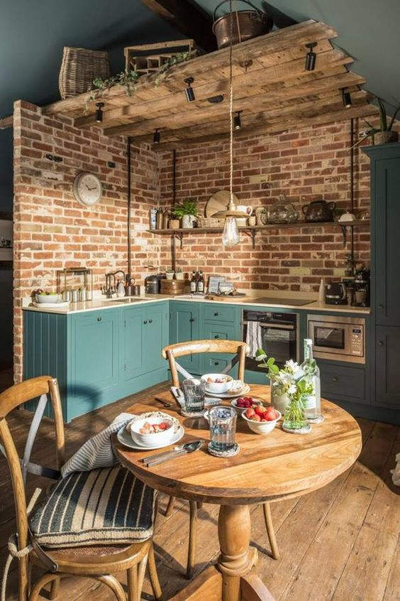 kitchen, wooden floor, brick wall, green wooden cabinet, wooden ceiling, pendant, white kitchen top, wooden round dining table, wooden chairs