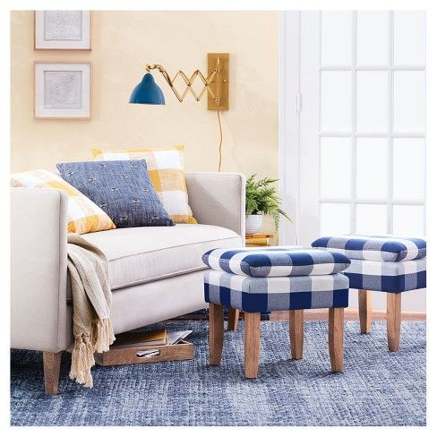 living room, blue rug, blue white stools, white sofa, pale yellow wall, blue sconce, white window frame
