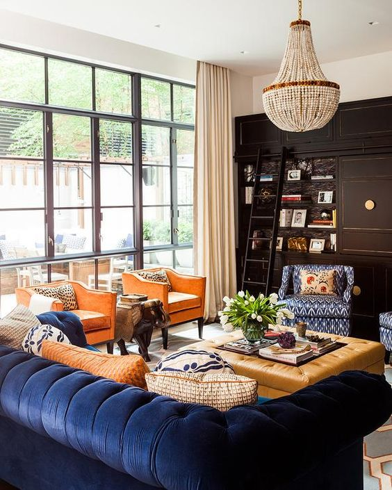 living room, blue rug with orange line, dark blue sofa, navy atterned chair, brown leather tufted ottoman, orange chairs, glass window, crystal chandelier, blackcabinet shelves