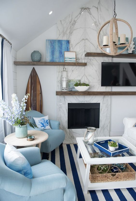 living room, blue white striped rug, white coffee table, white wall, white sloping ceiling, white sofa, blue chairs, round side table, floating shelves, pendant