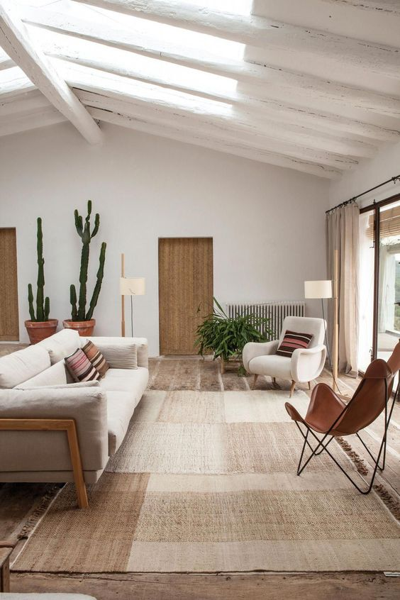 living room, brown floor, rattan rug, white sofa, white chair, brown leather. white wall, sliding doors