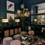 Living Room, Brown Patterned Rug, Dark Green Wall, Green Sofa, Glass Topped Coffee Table, Black Cabinet, Golden Table Lamp, Mirror, Glass Pendant